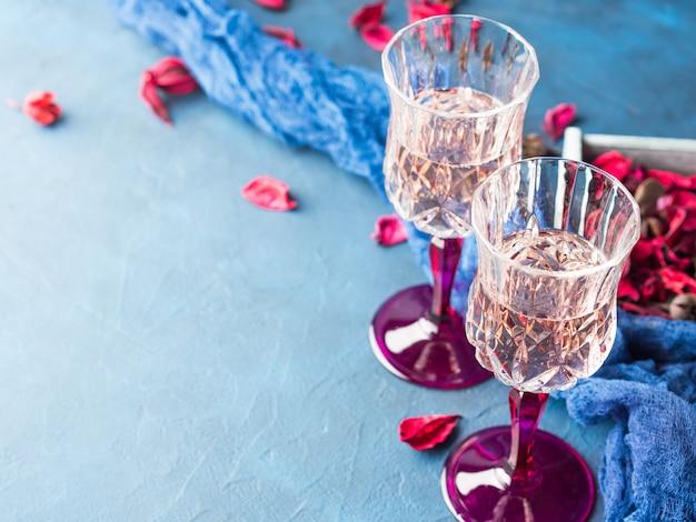 Dois proviveram vidros do champanhe em flores secadas cor-de-rosa textured do azul com. convite de data romântica de casamento de dia dos namorados