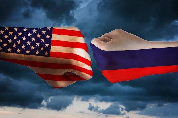 Dois punhos com as bandeiras da américa e rússia conceito de confronto entre estados