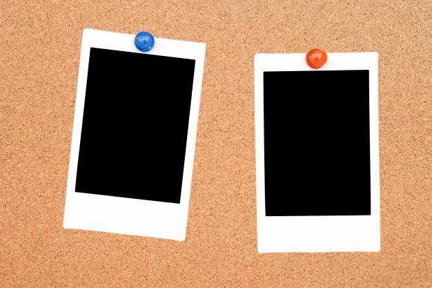 Dois quadros de foto instantânea em branco na placa de aviso de cortiça