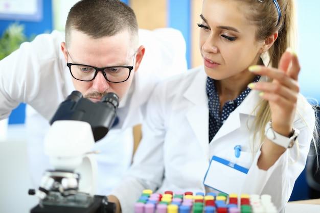 Dois químicos na reunião contra o fundo do laboratório de química.