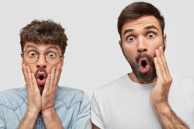 Dois rapazes chocados a olharem com olhos esbugalhados