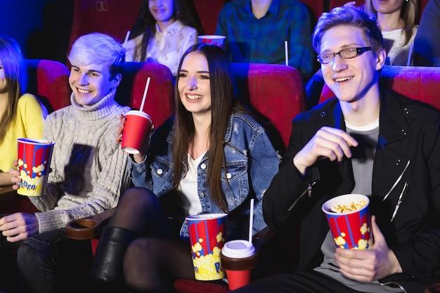 Dois rapazes e uma garota assistindo uma comédia no cinema. jovens amigos assistem filmes no cinema. grupo de pessoas no teatro com pipoca e bebidas
