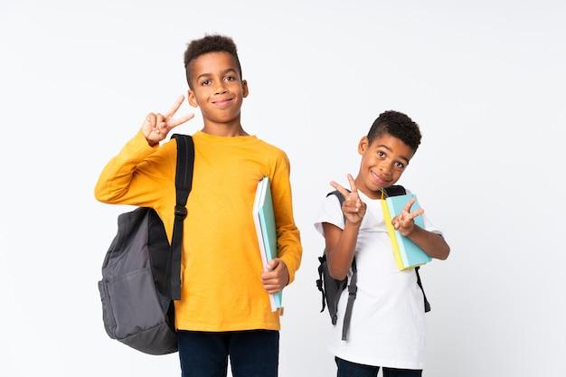 Dois rapazes estudantes afro-americanos sobre branco e fazendo gesto de vitória