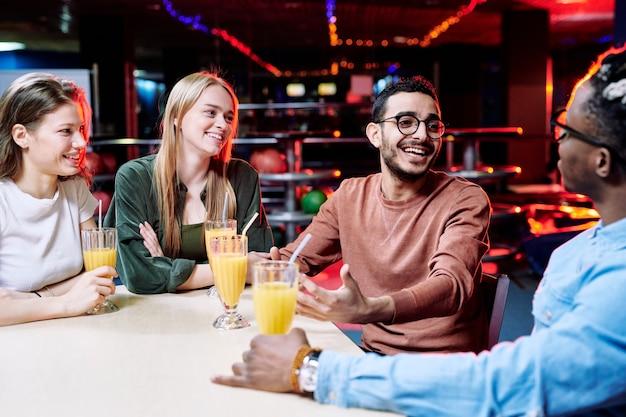 Dois rapazes multiétnicos felizes discutindo momentos curiosos do último jogo de boliche enquanto suas namoradas com bebidas sentadas perto