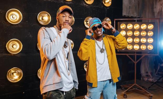 Dois rappers negros de boné no palco com holofotes
