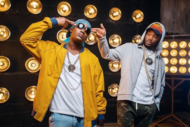 Dois rappers negros em bonés, artistas posam no palco com holofotes