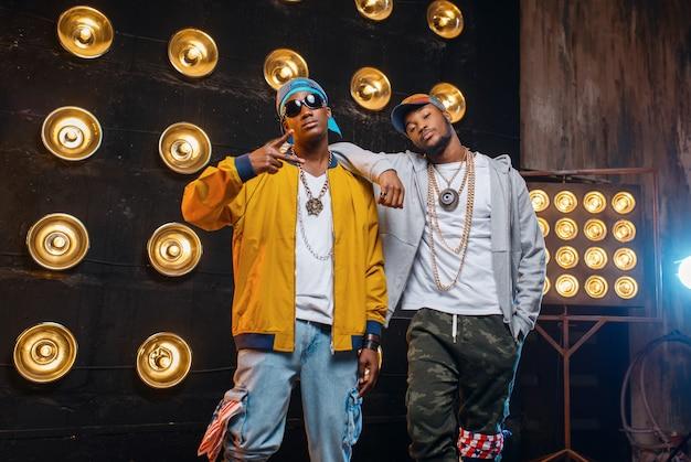 Dois rappers negros em bonés, artistas posam no palco