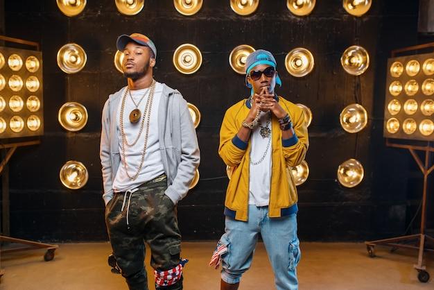 Dois rappers negros em bonés, atuando no palco