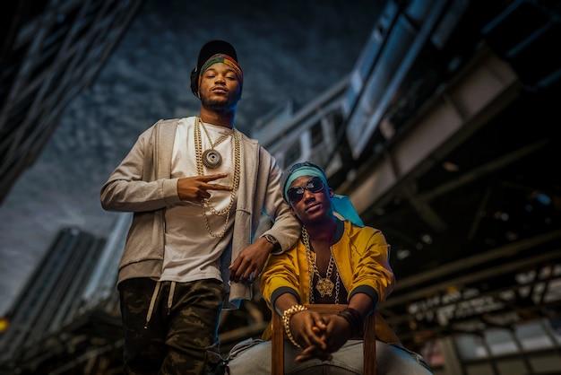Dois rappers negros posam na rua da cidade à noite, arranha-céus. artistas de rap contra a cidade, concerto de música underground, estilo urbano
