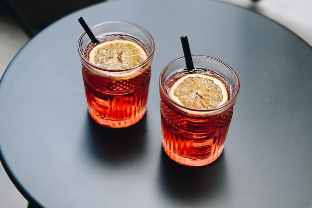 Dois refrescantes cocktails laranja com canudos pretos curtos sobre uma mesa de metal preto ao ar livre