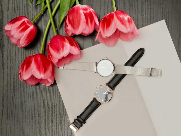 Dois relógios de pulso em uma folha cinza e tulipas, vista superior