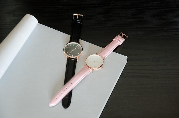 Dois relógios de pulso são pretos e rosa, em uma folha cinza