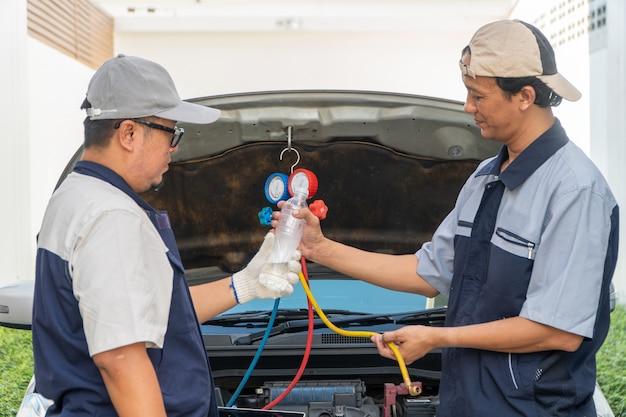 Dois reparadores de automóveis verificam o motor e o sistema de refrigeração antes de viajar de férias prolongadas.