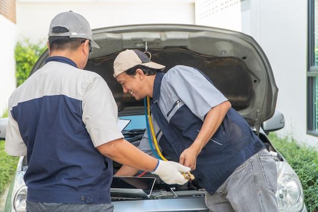 Dois reparadores de automóveis verificam o motor e o sistema de refrigeração antes de viajar de férias.