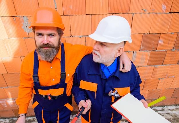 Dois reparadores trabalhando em um trabalhador de publicidade de construção em uma chave inglesa de martelo de reparador de capacete