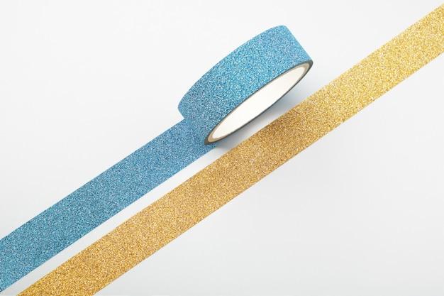 Dois rolos de fita de glitter e tiras paralelas em branco