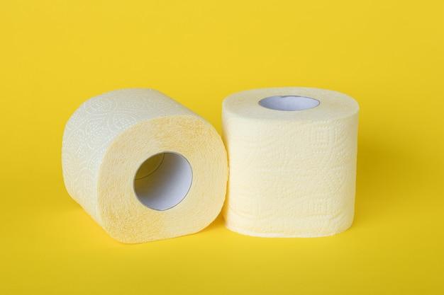 Dois rolos de papel higiênico em uma parede amarela. conceito de higiene pessoal.