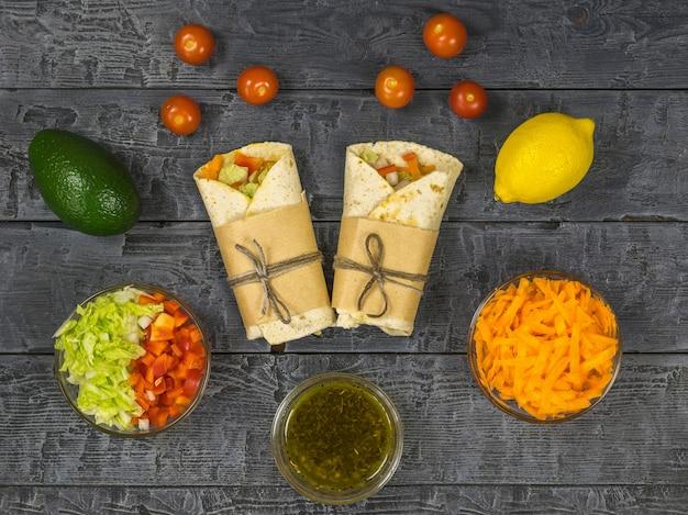 Dois rolos de vegetais e produtos vegetarianos em uma mesa de madeira escura. comida vegetariana.