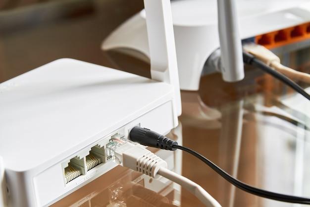 Dois roteadores sem fio brancos em uma mesa de vidro conectados por cabos à internet
