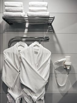 Dois roupões de banho brancos no banheiro na parede com um secador de cabelo branco e toalhas no hotel