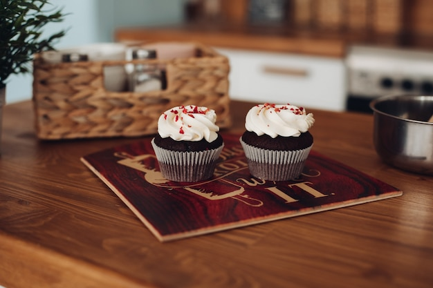 Dois saborosos cupcackes de chocolate com um creme branco