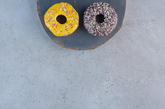 Dois saborosos donuts decorados com granulado na peça de madeira.
