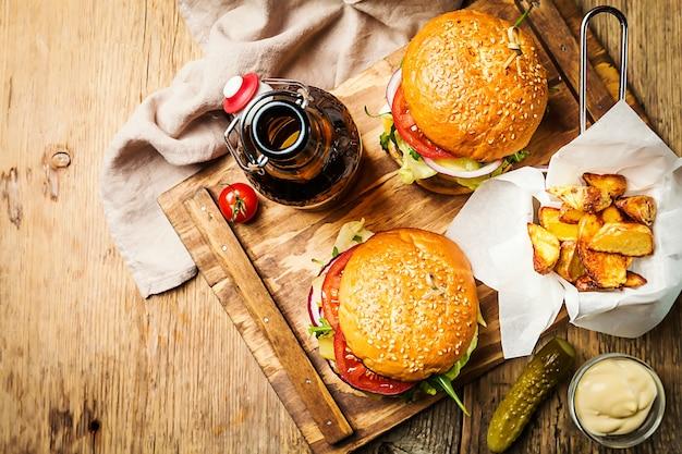 Dois saborosos hambúrgueres clássicos de carne grelhados com batatas fritas em uma mesa de madeira rústica com espaço de cópia