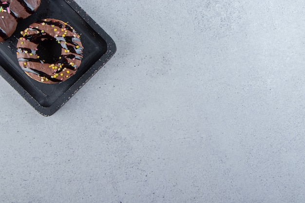 Dois saborosos mini bolos de chocolate com granulado na tábua de corte preta. foto de alta qualidade