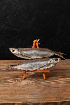 Dois sabrefish secos ao ar em um suporte de servir em fundo preto