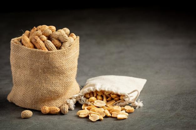 Dois sacos de amendoim colocados em fundo escuro