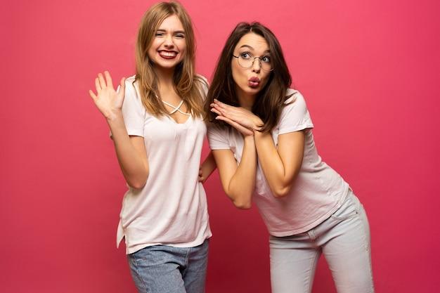Dois saíram da mulher se divertindo e levantando as mãos. de pé no fundo rosa. humor de sorte.