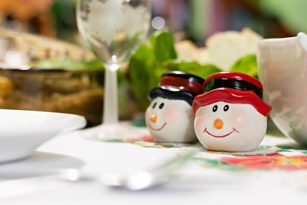 Dois saleiros em forma de cabeças de bonecos de neve em chapéus na mesa com ceia de natal
