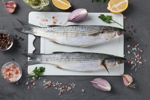 Dois salmonetes crus com ingredientes e temperos na placa de plástico branca sobre fundo escuro. vista de cima