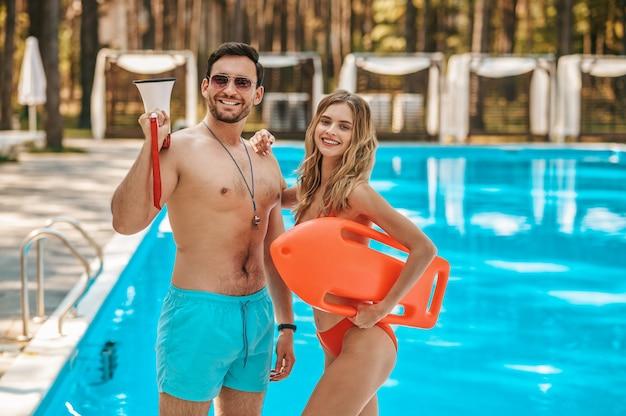 Dois salva-vidas de piscina em pé perto da piscina pública