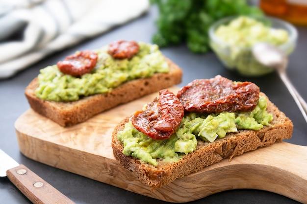 Dois sanduíches de abacate. pão de centeio com guakomole, macarrão de abacate e tomate seco, na tábua de madeira. torrada de abacate.