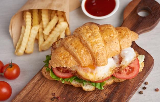 Dois sanduíches de croissant na mesa de madeira, vista de cima