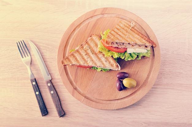 Dois sanduíches triangulares e azeitonas em uma placa redonda de madeira
