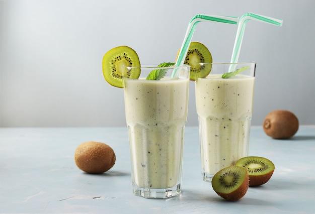 Dois saudáveis smoothie de desintoxicação de kiwi e banana em copos altos em azul claro