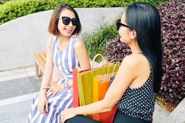 Dois shopaholics com sacolas de compras
