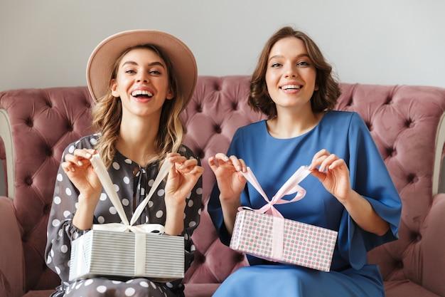 Dois shopaholics entusiasmado das jovens mulheres que guardam caixas atuais da surpresa.