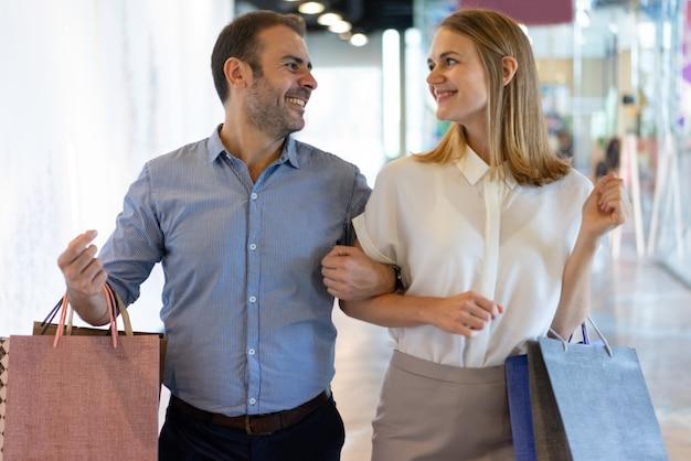 Dois shopaholics felizes que têm o grande tempo no shopping.
