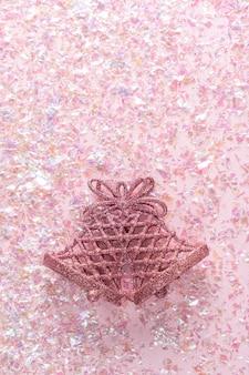 Dois sinos no rosa com enfeites de natal. natal mínimo. feliz ano novo. vista plana, vista superior, copyspace