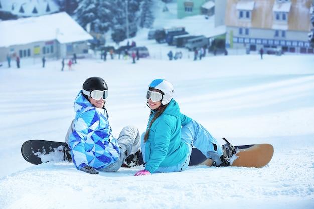 Dois snowboarders na pista de esqui em um resort nevado