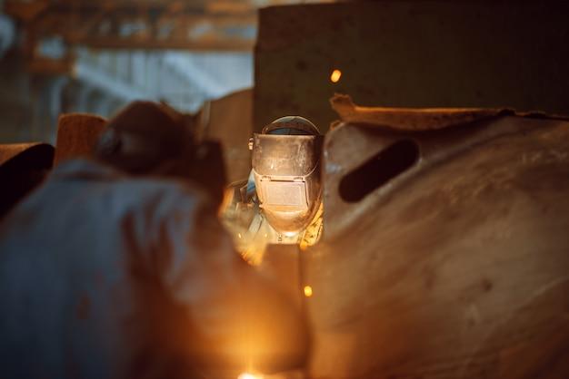 Dois soldadores em máscaras trabalham com metal