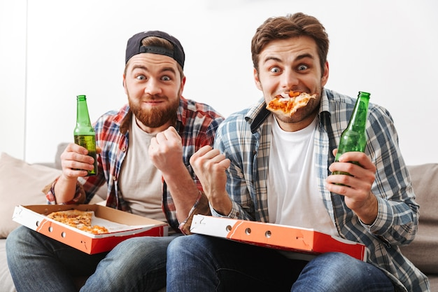 Dois solteiros emocionados se divertindo e regozijando na vitória de time de futebol, comendo pizza e bebendo cerveja em casa