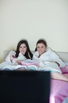 Dois, sorrindo, amigos, desgastar, bathrobes, tv assistindo, cama