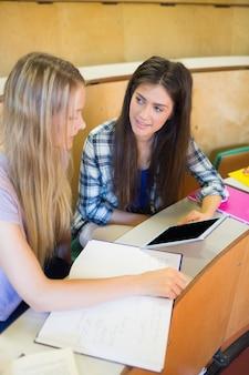 Dois, sorrindo, estudantes, usando, tabuleta, em, universidade