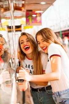 Dois, sorrindo, femininas, amigos, tendo divertimento, em, parque divertimento