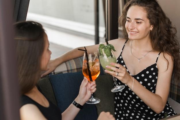 Dois, sorrindo, jovem, femininas, amigos, brindar, coquetel, óculos