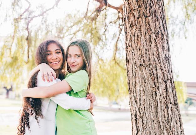 Dois, sorrindo, meninas, amigo, abraçar, um ao outro, sob, a, árvore